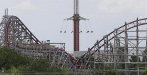 The Texas Giant roller coaster ride sits idle in the foreground as people take in another ride a the Six Flags Over Texas park Saturday, July 20, 2013, in Arlington, Texas.