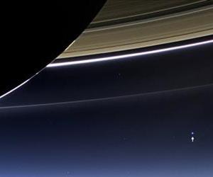 This July 19, 2013 image from the Cassini spacecraft shows the planet Earth, annotated by NASA with a white arrow, lower right, below Saturn's rings.