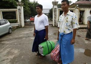 Win Thaw, left, and Win Hla, right, political prisoners who were released after receiving amnesty from President Thein Sein, stand outside the entrance of a prison today.