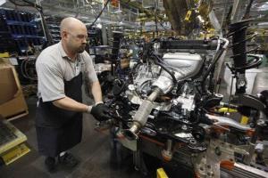 In this Dec. 14, 2011 photo, a line worker moves an engine on the assembly line for a Ford Focus at the Ford Michigan Assembly plant in Wayne, Mich.