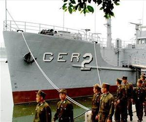 In this June 22, 2006 photo released by North Korea's Korea Central News Agency, North Korean soldiers watch USS Pueblo, which was seized by North Korean navy off the Korean coast in Jan. 1968.