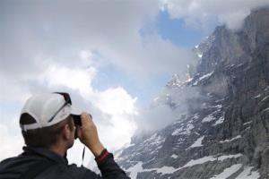 On July 11, 2013, a journalist photographs the Eiger north face on the 75th anniversary of the its ascent above the Kleine Scheidegg, Switzerland.