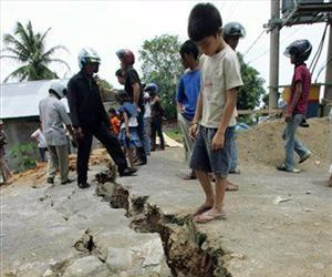 Indonesian youth look at a crack on the ground following a strong earthquake in Bengkulu, Sumatra island, Indonesia, Thursday, Sept. 13, 2007.