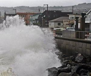 Waves pound a wall near buildings in Pacifica, Calif.