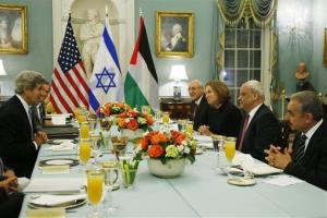 Secretary of State John Kerry sits with Israeli and Palestinian negotiators at a State Department dinner Monday night.
