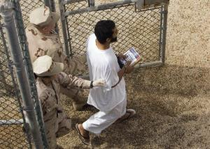 Guards escort a Guantanamo detainee carrying a book from the detainee library trailer to the detention facility.
