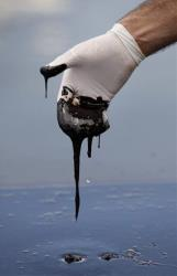 A glove reaches into thick oil on the surface of the northern regions of Barataria Bay in Plaquemines Parish, Louisiana.