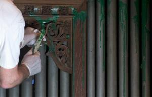A worker removes green paint from the organ in the Washington National Cathedral's historic Bethlehem Chapel.