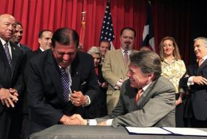 Texas State Senator Eddie Lucio Jr., left, and Gov. Rick Perry share a laugh Tuesday, July 16, 2013 at UTPA in Edinburg, Texas.