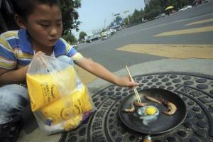 In this photo taken on Wednesday, a child demonstrates how raw shrimp and an egg are fried in a pan on a manhole cover in Jinan, China.