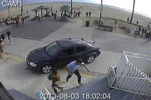 In this image take from security video, pedestrians scatter as a car drives through a packed crowd along the Venice Beach boardwalk, Saturday, Aug. 3, 2013.