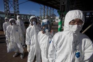 Workers in protective suits and masks wait to enter the emergency operation center at the crippled Fukushima Dai-ichi nuclear power station.