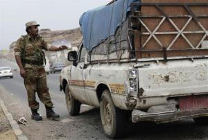 A Yemeni soldier stops a car at a checkpoint in a street leading to the US embassy in Sanaa, Yemen, Sunday.