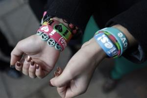 In this Feb. 20, 2013 photo, Easton Area School District students Brianna Hawk, 15, left, and Kayla Martinez, 14, display their bracelets for photographers outside the US Courthouse in Philadelphia.