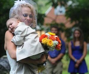 Christine Swidorsky carries her son and the couple's best man, Logan Stevenson, 2, down the aisle on Aug. 3.