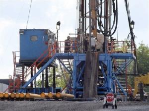 In this 2012 file photo, a crew works on a drilling rig at a well site for shale-based natural gas in Zelienople, Pa.
