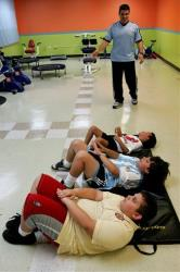 Children's fitness expert Jose Ortiz helps train boys in abdominal exercises, at the gym he operates in Guaynabo, Puerto Rico, April 20, 2007.