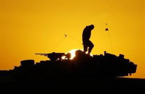 FILE - A U.S. soldier walks atop his armored vehicle at sunset as he prepares for a nighttime military exercise in the Kuwaiti desert south of the Iraqi border on Sunday, Dec. 22, 2002. Combat appears to have little or no influence on suicide rates among U.S. troops...