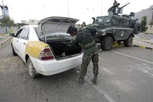 A policeman checks a car at a checkpoint near the US embassy in Sanaa, Yemen, Tuesday.