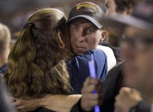 Firefighter Brendan McDonough embraces a mourner near the end of a candlelight vigil in Prescott, Arizona.
