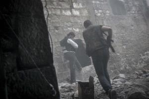 In this Saturday, Nov. 03, 2012 photo, rebel fighters run for cover through smoke from an explosion.
