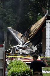 A firefighter surveys the scene of a small plane crash Friday in East Haven, Conn.