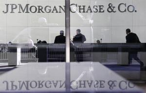 In this May 11, 2012 file photo, people stand in the lobby of JPMorgan Chase headquarters in New York.