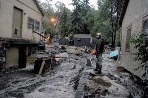 Volunteer rescuer Jesse Rochette searches the Fountain Creek flood waters for anyone trapped or stranded as another flash flood washes off the Waldo Canyon burn scar, Friday, Aug. 9, 2013 in Manitou, Colo. A mudslide has closed U.S. 24 between Cascade and Manitou Springs, and flash flooding in Manitou...