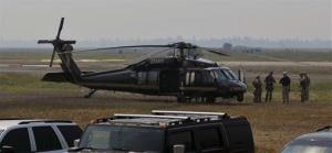 Authorities wait near a blackhawk helicopter at the Cascade Airport in Cascade, Idaho, Saturday.