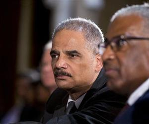 Attorney General Eric Holder, left, attends a ceremony on Capitol Hill in Washington, Wednesday, July 31, 2013, in observance of the 50th anniversary of the March on Washington for Jobs and Freedom.