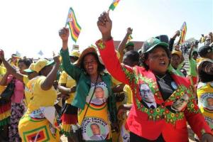Supporters of Robert Mugabe sing and dance at the country's celebration of  Heroes Day in Harare, Monday, Aug. 12, 2013.