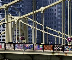 Pedestrians walk across the Andy Warhol bridge on Monday, Aug. 12, 2013 in Pittsburgh. More that 1,800 knitters covered it in 3,000 feet of colorful yarn.