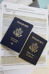 Am enhanced United States passport lies, at left, beside an expired pierced passport.