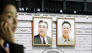 A woman uses her mobile phone near a screen showing the portraits of North Korean national founder the late Kim Il Sung, left, and late leader Kim Jong Il, right.