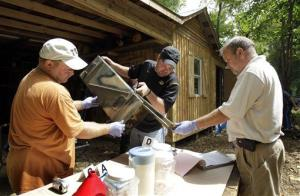 In this Sept. 2, 2010 file photo, Franklin County Detective Jason Grellner, center, sorts through evidence with a detective and an officer during a raid of a suspected meth house in Gerald, Mo.