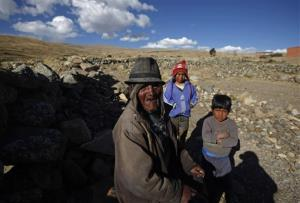 Carmelo Flores Laura, a native Aymara, poses for a photo with his great-grandchildren outside his home in the village of Frasquia, Bolivia, Tuesday, Aug. 13, 2013.