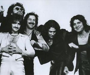 Blue Oyster Cult publicity photo from 1977. Left to right: Donald Buck Dharma Roeser (white shirt); behind him Eric Bloom (sunglasses); Albert Bouchard; Allen Lanier; Joe Bouchard.