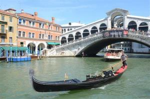 A gondola plies the waters of Venice's Grand Canal, Italy.
