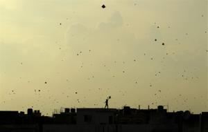 In this Thursday, Aug. 15, 2013 file photo, a boy flies a kite from the roof of a house as those flown by others dot the sky in New Delhi, India.