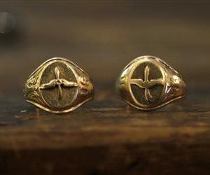 This Friday, Aug. 16, 2013 photo taken in Raleigh, N.C., shows a pair of gold aviator rings, a replica, right, of the original ring, at left, that belonged to U.S. Army Air Corps 2nd Lt. David C. Cox.