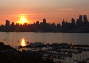 In this Aug. 15, 2003 file photo, the sun rises over the skyline of the Upper West side of Manhattan as seen from Weehaken, NJ.