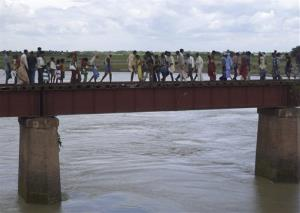 Indian villagers walk through a railway bridge after a train ran over a group of Hindu pilgrims at a crowded station in Dhamara Ghat, Bihar state, India.