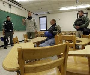 FBI instructor Mike Copeland, second from left, prepares local police officers for an active shooter drill in a college classroom in Salisbury, Md., Aug. 13, 2013.
