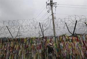A man touches ribbons with messages wishing for the Koreas' reunification on military wire fences at the Imjingak Pavilion near the border village of Panmunjom, Wednesday, Aug. 7, 2013.