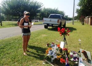 Sarah Harper, Christopher Lane's girlfriend, stands beside a memorial along the road where police say Lane was killed in Duncan, Okla.