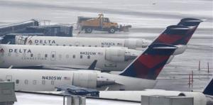 A truck with a plow drives pass Delta planes parked at their gates at the Salt Lake City Airport Thursday, Jan. 24, 2013.