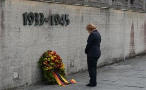 German Chancellor Angela Merkel attends a wreath laying ceremony during her visit to the concentration camp Dachau in southern Germany, on Tuesday, Aug.20, 2013.
