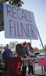 Greg Timms signs a petition to recall San Diego Mayor Bob Filner at a stand set up in the parking lot of a shopping center Wednesday, Aug. 21, 2013, in San Diego.