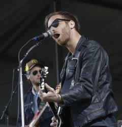 Dan Auerbach, foreground, performs with his band The Black Keys, the New Orleans Jazz and Heritage Festival in New Orleans, Sunday, May 5, 2013.
