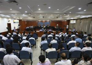 This photo released by the Jinan Intermediate People's Court shows people at the trial of disgraced politician Bo Xilai, center top with white shirt.